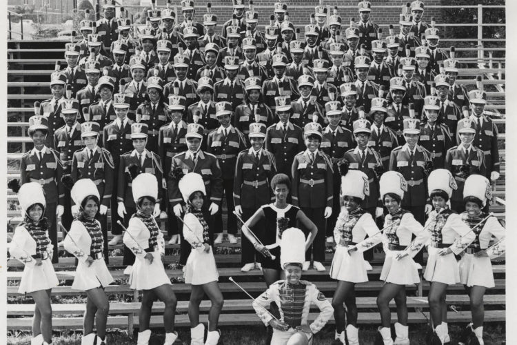 Women pose in marching costumes on risers